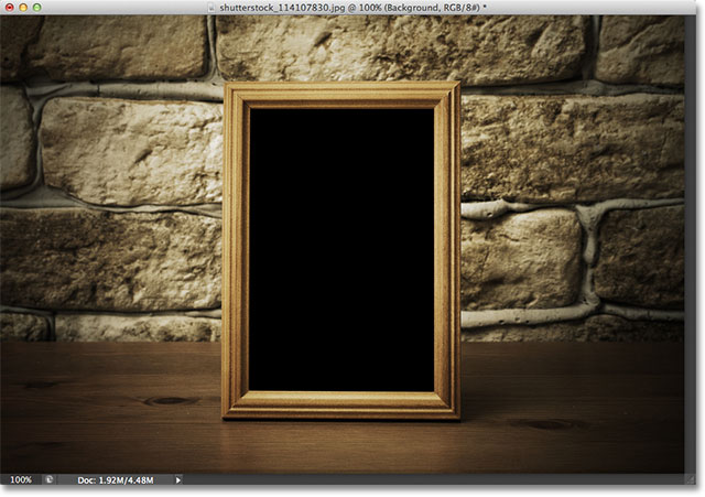 Old photo frame on the wooden table. Image licensed from Shutterstock by Photoshop Essentials.com