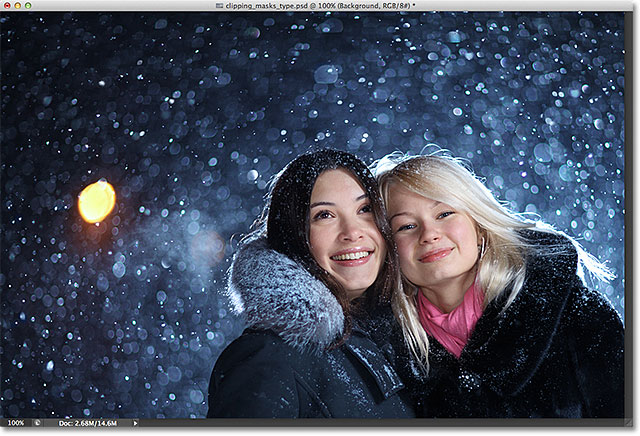Two happy young female friends enjoying snowfall on Christmas winter night over snow background. Image licensed from Shutterstock by Photoshop Essentials.com