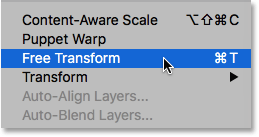 Selecting the Free Transform command from under the Edit menu. Image © 2016 Photoshop Essentials.com