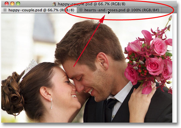 Dragging the first photo onto the name tab of the second photo. Image © 2011 Photoshop Essentials.com