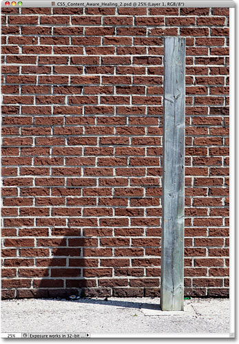 A photo of a wooden post casting a shadow against a brick wall. Image © 2010 Steve Patterson, Photoshop Essentials.com