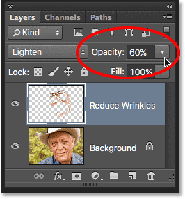 Lowering the opacity of the Reduce Wrinkles layer. Image © 2016 Photoshop Essentials.com