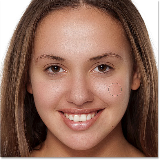 Painting with white on the layer mask to reveal the skin softening effect on her nose, cheeks, and around her eyes. Image © 2016 Steve Patterson, Photoshop Essentials.com