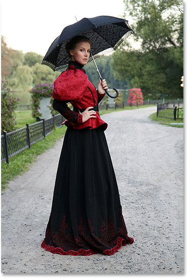 Girl with an umbrella in a vintage suit in a park. Image licensed from Shutterstock