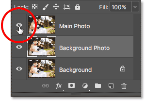 Clicking the visibility icon for the 'Main Photo' layer to hide it in the document. Image © 2017 Photoshop Essentials.com.