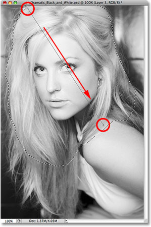 Dragging a white-to-transparent gradient through the selected area. Image © 2009 Photoshop Essentials.com