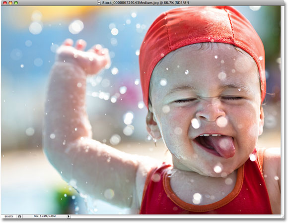 A photo of a young boy playing in the water. Image licensed from iStockphoto by Photoshop Essentials.com.