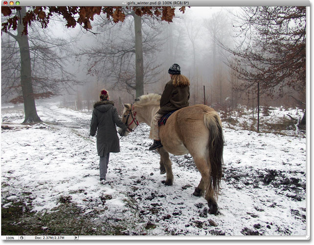 The original photo of two girls with a horse walking through the snow. Image licensed from iStockphoto by Photoshop Essentials.com.