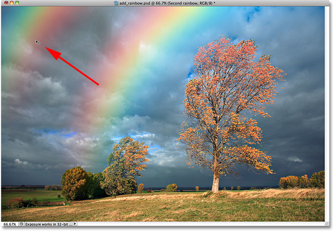 Dragging the second rainbow into place in the document. Image © 2010 Photoshop Essentials.com