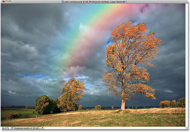 The layer mask has been applied to the second rainbow. Image © 2010 Photoshop Essentials.com