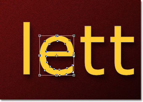 The Free Transform bounding box and handles appears around the letter. Image © 2011 Photoshop Essentials.com.