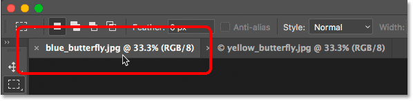 Clicking the tabs to switch between grouped documents in Photoshop.