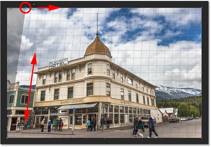 Correcting perspective by matching the grid line with the left side of the building in Photoshop