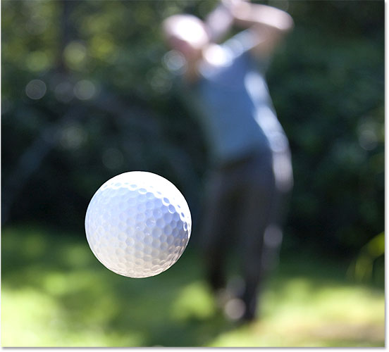 A golf ball in flight. Image #24403595 licensed from Adobe Stock by Photoshop Essentials.com