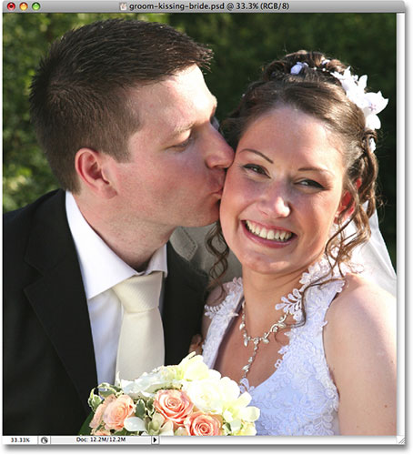 A wedding photo of a groom kissing the smiling bride.