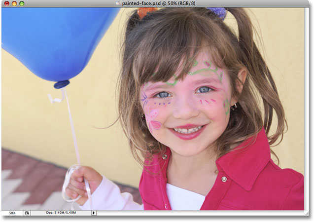 A photo of a young girl with a painted face holding a balloon. Image used by permission from iStockphoto.com
