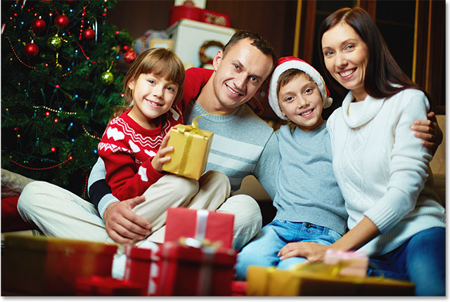 Portrait of friendly family looking at camera on Christmas evening. Image 115748269 licensed from Shutterstock by Photoshop Essentials.com