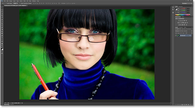 young thinking woman in glasses with pen. Image licensed from Shutterstock by Photoshop Essentials.com