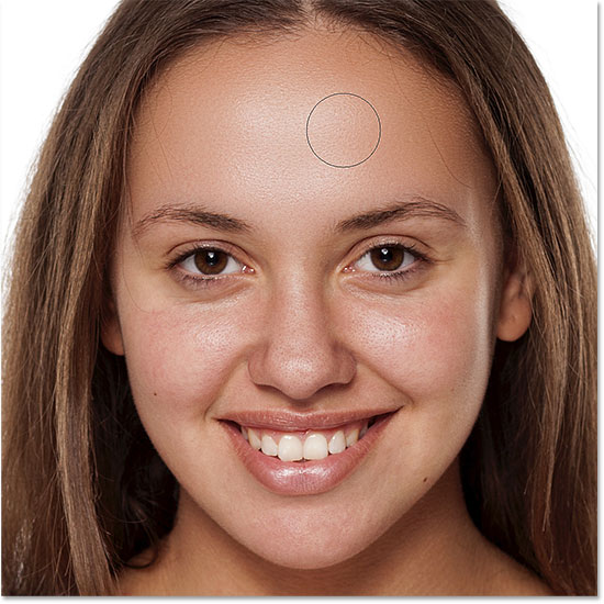 Painting to reveal the smooth skin in the woman's forehead in Photoshop
