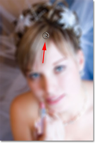 Dragging the initial pin away from the woman's eyes in the photo. Image © 2012 Photoshop Essentials.com