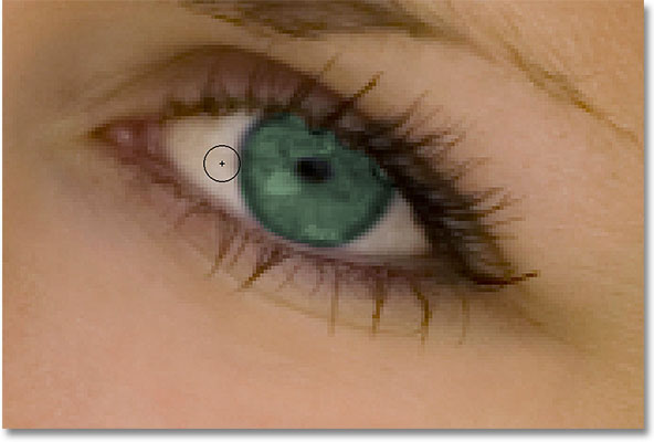 Painting around the eye with black to hide the Hue/Saturation adjustment layer. Image © 2010 Photoshop Essentials.com