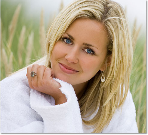 A photo of a woman in a white robe sitting in tall grass. Image licensed from iStockphoto by Photoshop Essentials.com