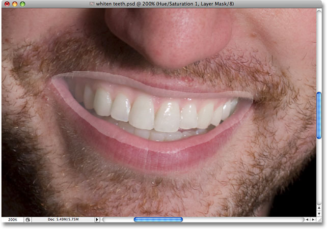 After brightening his teeth, the rest of the selected area has also been brightened.   Image © 2008 Photoshop Essentials.com.