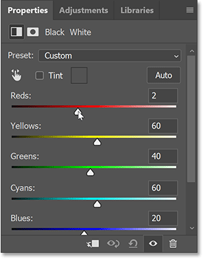 Dragging the color sliders for the Black and White adjustment layer in the Properties panel.