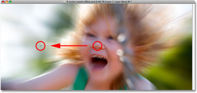 Dragging a Radial Gradient on the layer mask in Photoshop.