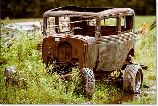 An old, rusted vintage car.