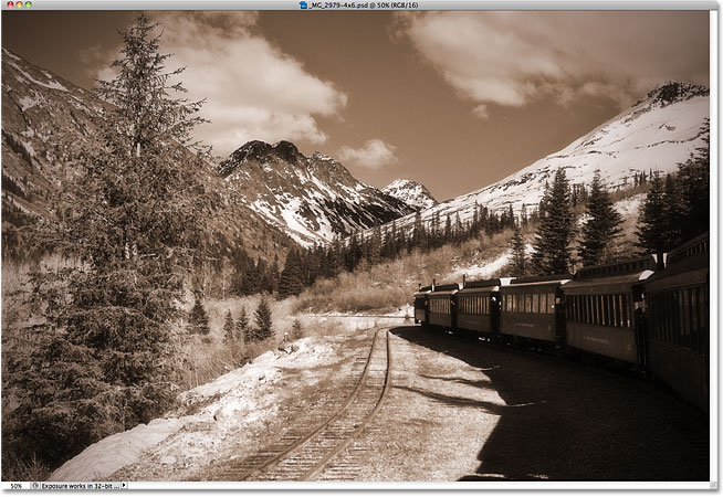 A sepia-toned photo of a train heading off into the mountains.