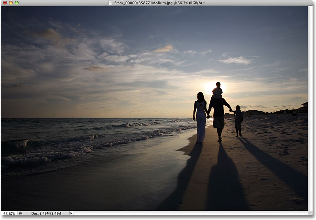 A family walking on the beach at sunset. Image licensed from iStockphoto by Photoshop Essentials.com.