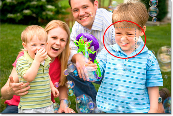 Using the Rectangular Marquee tool to drag a square selection around the boy's face.