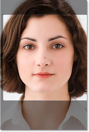 Using the Crop Tool to drag a selection around the woman's face.