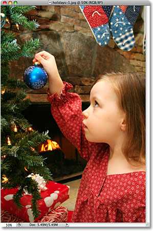 A photo of a girl placing an ornament on a Christmas tree. Image licensed from iStockphoto by Photoshop Essentials.com.