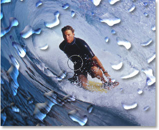 Erasing the water drops in front of the surfer with the Eraser Tool.