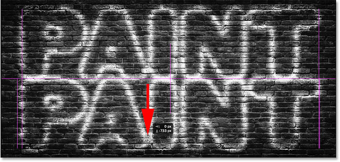 Dragging the copy of the spray-painted text effect to the bottom of the image in Photoshop