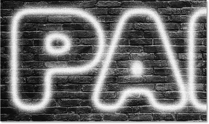 Paint speckles have been added to the spray paint text effect in Photoshop